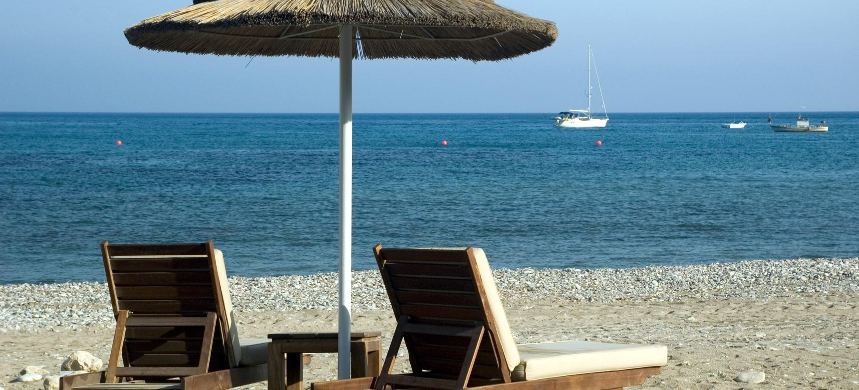 Big beach parasol two chaise longues
